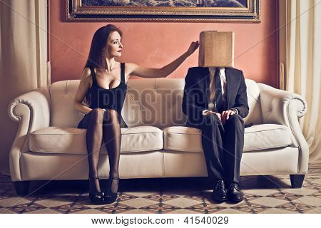 Elegant redhead woman sitting on a white sofa touching a box that covers the face of a businessman on the sofa
