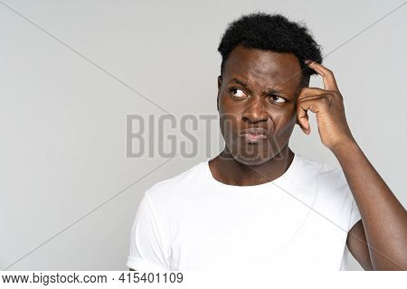 Studio Portrait Of Unsure Doubtful African Man Scratching Head, Looking Left Doubtfully At Copy Spac
