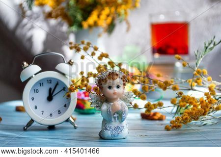 Easter Greeting Card. Festive Composition With Mimosa Flowers, Angel And Clock Eve Of The Holiday, O