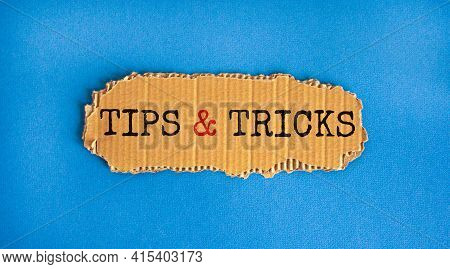 Tips And Tricks Symbol. Words 'tips And Tricks' On Brown Paper. Beautiful Blue Background. Business,
