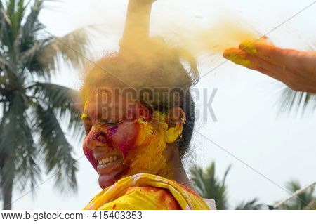 Portrait Of One Young Indian Happy Woman With Pink, Yellow And Red Holi Colored Powder Paint On Face