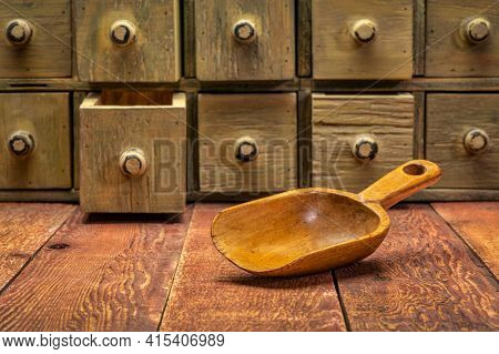 wooden scoop and primitive wooden apothecary or catalog cabinet, rustic theme or storage and sorting concept