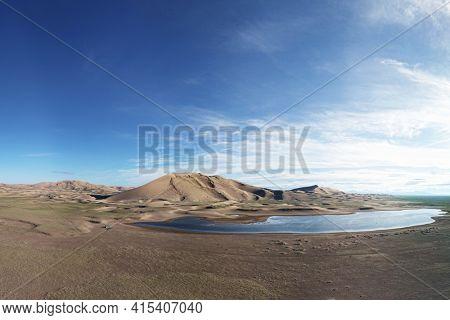 A large lake on the edge of a sandy desert. Mongolia sandy dune desert Mongol Els. Khovd province, Western Mongolia.