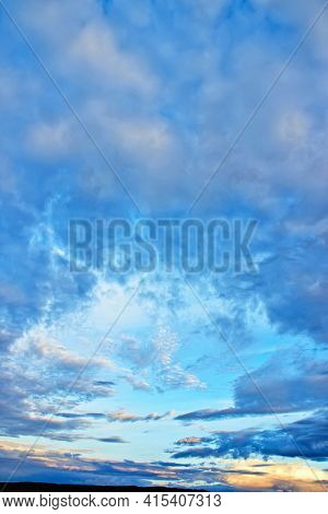 Majestic sunset sky background with gentle colorful clouds without birds.