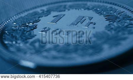 1 Swiss Franc Coin Close-up. Dark Blue Background Or Wallpaper On An Economic, Business, Entrepreneu