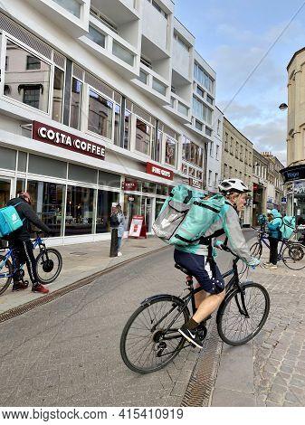 Cambridge, United Kingdom - April 2, 2021: Deliveroo Riders In Cambridge City Center