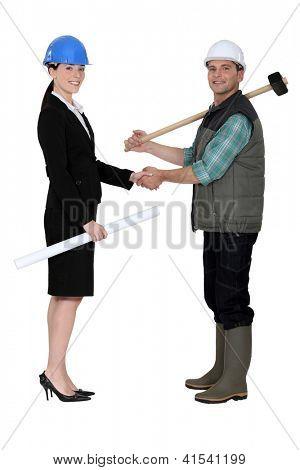 Businesswoman greetin manual worker