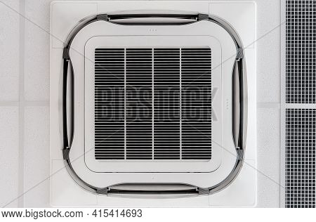 Ceiling Mounted Cassette Type Air Condition Unit Located Inside Commercial Hall With Hanging Light A