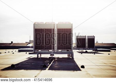 Air Vents On The Roof Of Building In Functional And Operational Condition. Sky Is Lit With Bright Li