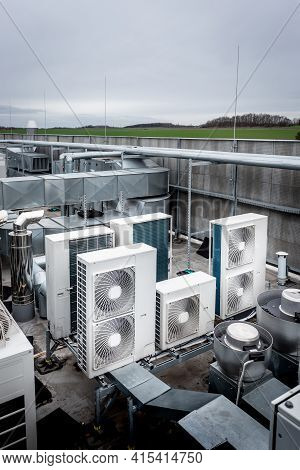 Square Air-conditioning Units On The Roof With Round Fan Grills. In Background Gradually Receding Ot