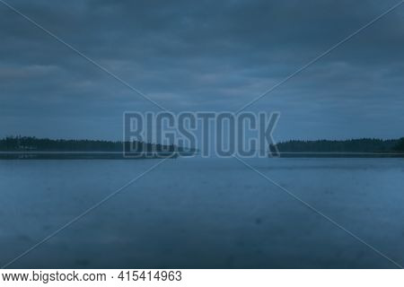 Moody Frozen Lake In Wilderness With Forest On Horizon And Cloudy Sky. Ice Is Partially Melted. Tree