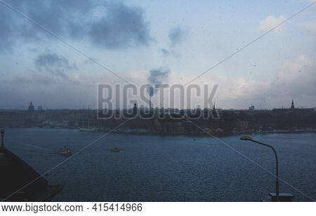 Winter Cityscape Of Seaside Town (stockholm) With Falling Snow And Light Fog, Which Underlines Nordi