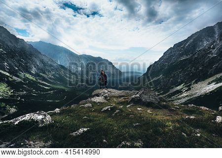 Young Couple In Middle Of Alpine Wilderness Surrounded By Mountains With Panoramic Views Of Wooded V