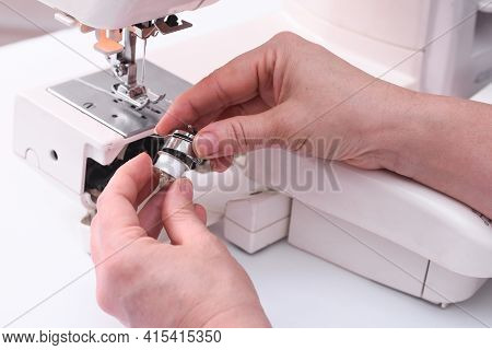 The Tailor Places The Bobbin In The Bobbin Cap Of The Sewing Machine.