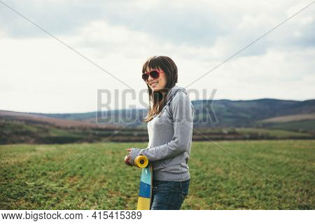 Young Smiling Girl In Sweatshirt Leaning On Her Longboard. In The Background Out Of Focus Are Grassy