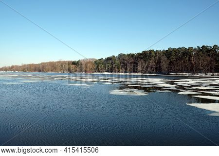 Natural Landscape With Open Water And Ice Drift On The Spring River And Forest Trees On Opposite Ban