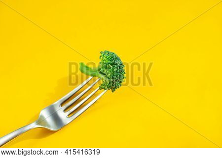 Fresh Broccoli On Fork Isolated On Yellow Background. Healthy Lifestyle Concept