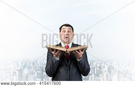 Surprised Businessman Holding Open Old Book. Startled Adult Man In Business Suit And Tie Standing On