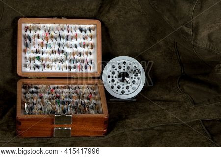 Trout Fly Reel And Wooden Fly Box On An Outdoor Coat