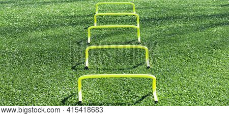 Five Yellow Mini Banana Hurdles In A Row For Runners To Perform Sports Drills Over During Speed And
