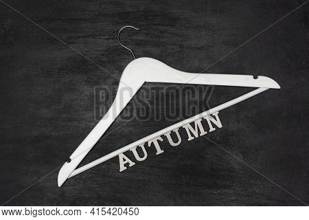 White Wooden Coat Hanger And Inscription Autumn On Black Background. Autumn Clothing Collection.