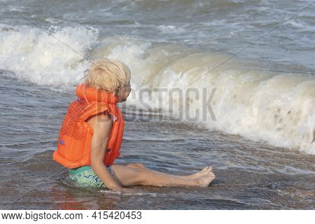 Light-haired Boy In An Orange Inflatable Vest Sitting On Seashore And Waiting For Waves.