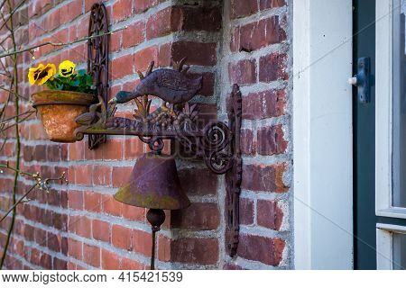Vintage Door Bell With Metal Duck And Flower Pot On The Red Brick Wall