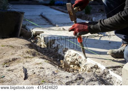 Defocus Bricklayer Removing Irregularities On Floor Screed With Hammer And Chisel. Male Hands In Red