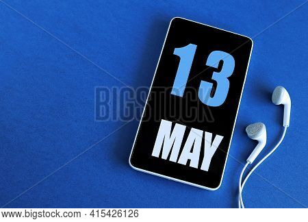 May 13. 13 St Day Of The Month, Calendar Date. Smartphone And White Headphones On A Blue Background.