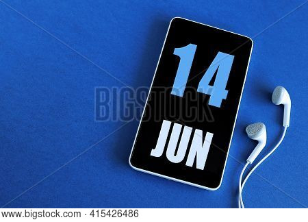 June 14. 14 St Day Of The Month, Calendar Date. Smartphone And White Headphones On A Blue Background