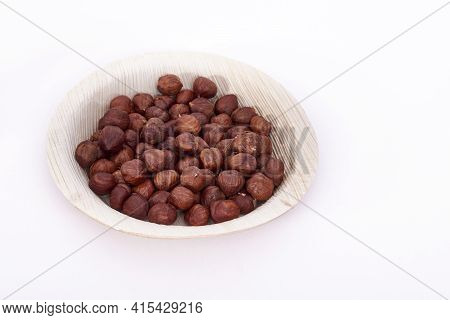 Areca Leaf Bowl Of Hazel Nuts On A White Background