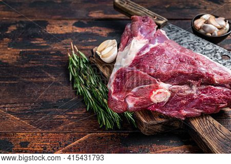 Uncooked Raw Mutton Lamb Thigh On Butcher Board With Meat Cleaver. Dark Wooden Background. Top View.