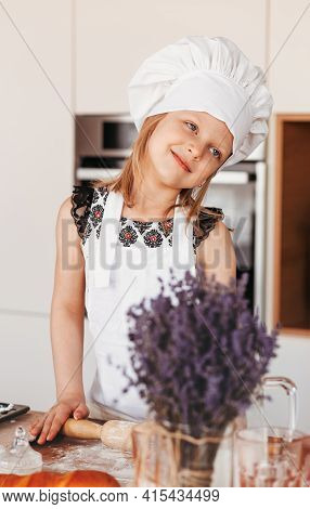 A Little Cute Girl With A Rolling Pin For Dough In The Kitchen. The Child Cooks Buns. Children Cook