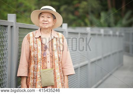 Old Elderly Female Elder Woman Traveller Traveling On Footbridge In Park. Senior Lifestyle