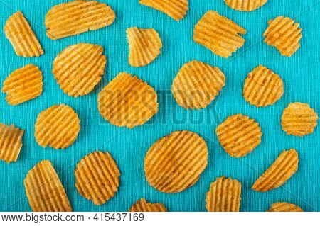Potato Chips, Grooved Gold Chips, Corrugated Crispy Snacks On A Turquoise Background, Colored Patter