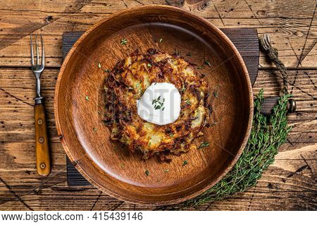 Roasted Potato Pancakes Or Fritters With Herbs In A Wooden Plate. Wooden Background. Top View