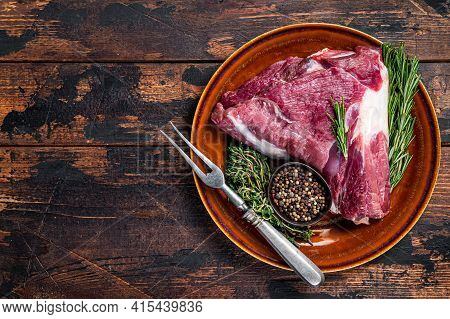 Raw Lamb Mutton Thigh Or Leg With Rosemary And Thyme In Rustic Plate. Dark Wooden Background. Top Vi