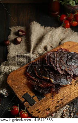 Delicious Smoked Sausage On A Dark Wooden Board With Tomatoes And . Delicious Handmade Snack Made Fr