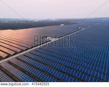 Aerial Drone View Into Large Solar Panels At A Solar Farm At Bright Sunset. Solar Cell Power Plants.