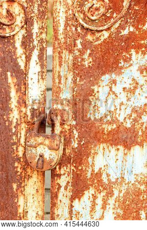 An Old Rusty Lock Connects The Leaves Of The Rusty Gate. The Texture Of A Metal Rusty Sheet.