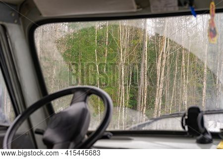 The View From The Car Through The Dirty Windshield Of The Forest. View From The Drivers Seat Of The