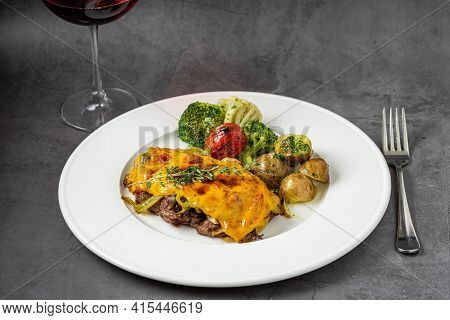 Cheddar Cheese Beefsteak With Potatoes And Broccoli On Dark Stone Background