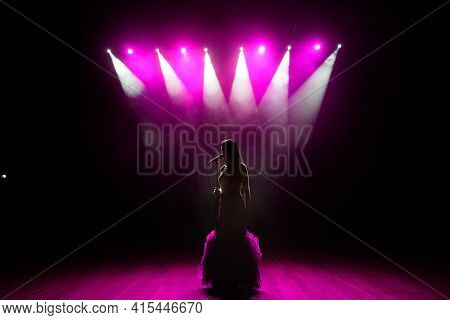 Girl In Long Gown Performing On Stage. Girl Singing On The Stage In Front Of The Lights. Silhouette