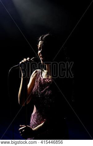 Singer Woman On Stage. Female Singer On The Stage Holding A Microphone.