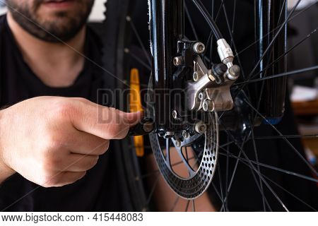 Hands Of A Mechanic Adjusting The Wheel Of A Bicycle To Its Crank. Bicycle Assembly.