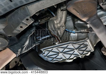 Oil Drains From From Beneath Vehicle As Mechanics Gloved Hand Removes Filter During Routine Maintena