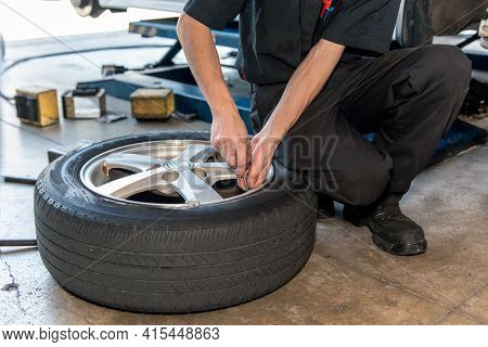 Mechanics Kneeling Next To Tire Adjusts The Inflated Tire Pressure Of Vehicle Front Tire During Rout