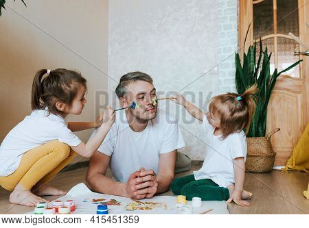 Children Have Fun With Their Father. Girls Draw On The Skin Of A Man's Face With Colorful Paints. Cr