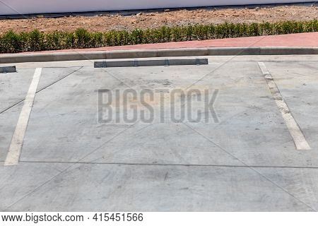 Wheel Stop Concrete Of Outdoor Parking, Concrete Wheel Stopper, Parking Space. Sign On The Road Of P