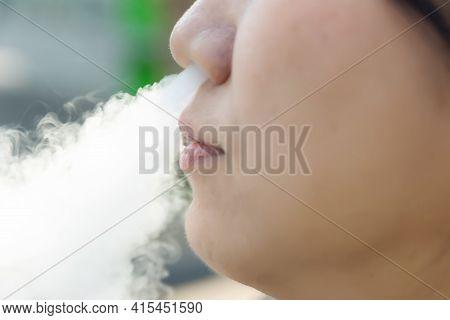 Smoking A Cigarette Smoke. Woman Smoking An E-cigarette. Glamorous Smoke Electronic Cigarette.